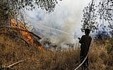 An Israeli soldier extinguishes a fire sparked by an incendiary balloon launched from the Gaza Strip, in a forest next to Kibbutz Nahal Oz in southern Israel, on June 26, 2019. (Menahem Kahana/AFP)