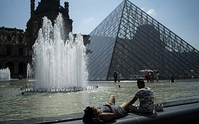 People sunbath in front of the Louvre Pyramid (Pyramide du Louvre) during a heatwave in Paris on June 26, 2019. (Kenzo TRIBOUILLARD / AFP)