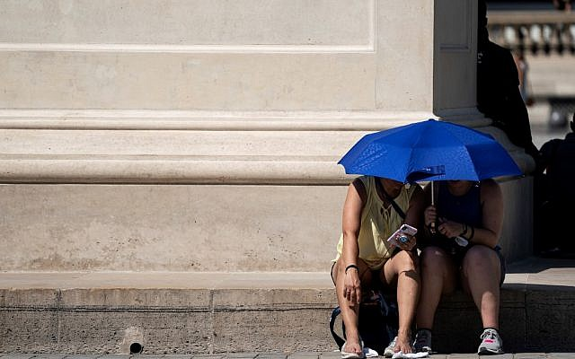 People use an umbrella to shelter from the sun near the Louvre Pyramid (Pyramide du Louvre) during a heatwave in Paris on June 26, 2019. (Kenzo TRIBOUILLARD / AFP)