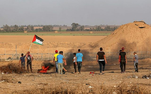 A Palestinian protester waves the national flag during a demonstration along the fence east of Khan Yunis in the southern Gaza Strip on June 26, 2019. (Said Khatib/AFP)