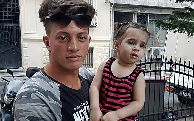 Algerian citizen Fawzi Zabaat (L), 17, poses with Syrian toddler Doha Muhammed he caught as she was falling from the second floor at Fatih district in Istanbul on June 27, 2019. (STR / DHA / AFP)