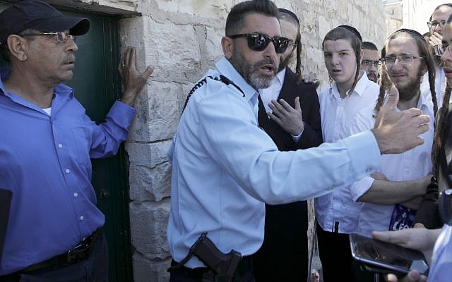 An Israeli policeman prevents ultra-Orthodox Jewish men from entering the Tomb of the Kings site owned and administered by the French Consulate of Jerusalem because they did not pre-register their visit through the internet which they do not use for religious reasons, in East Jerusalem on June 27 2019. (Photo by MENAHEM KAHANA / AFP)