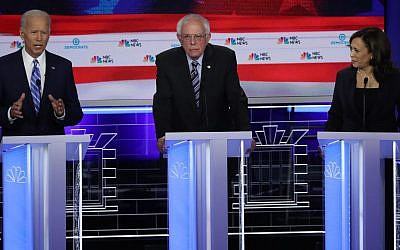 Sen. Kamala Harris (R) (D-CA) and former Vice President Joe Biden (L) speak as Sen. Bernie Sanders (I-VT) looks on during the second night of the first Democratic presidential debate in Miami, Florida on June 27, 2019. (Drew Angerer/Getty Images via JTA)