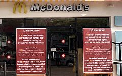 Signs placed in front of McDonald's branches in Tel Aviv on June 4, 2019, accusing the fast-food chain of boycotting West Bank settlements, and urging Israelis to boycott the restaurant giant in return. (Channel 12 screen capture)