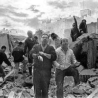 Firemen and civilians walk over the rubble left after a bomb exploded at the AMIA Jewish center in Buenos Aires, Argentina, July 18, 1994. (Ali Burafi/AFP/Getty Images/via JTA)