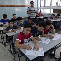 In this May 26, 2019, photo, a teacher supervises while Palestinian schoolchildren take a final exam during the last day of the school year, at the UNRWA Hebron Boys School, in the West Bank city of Hebron. (AP Photo/Nasser Nasser)