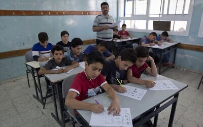 Illustrative: In this May 26, 2019 photo, a teacher supervises while Palestinian schoolchildren take a final exam during the last day of the school year, at the UNRWA Hebron Boys School, in the West Bank city of Hebron. (AP Photo/Nasser Nasser)