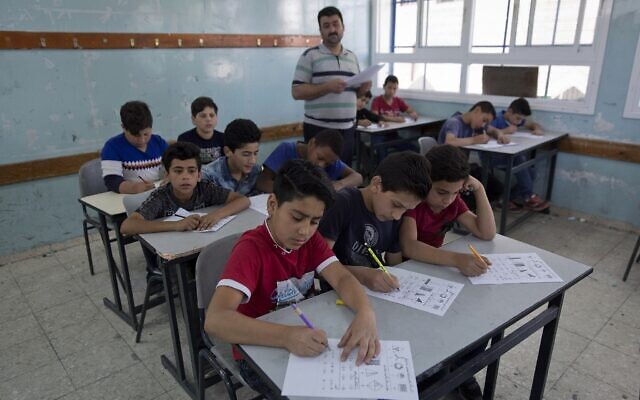 Illustrative: In this May 26, 2019, photo, a teacher supervises while Palestinian schoolchildren take a final exam during the last day of the school year, at the UNRWA Hebron Boys School, in the West Bank city of Hebron. (AP Photo/Nasser Nasser)