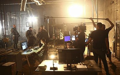 "In this May 30, 2019 photo, a crew films a scene on the set of Israel's hit TV show ""Fauda,"" in Tel Aviv, Israel. (AP Photo/Oded Balilty)"