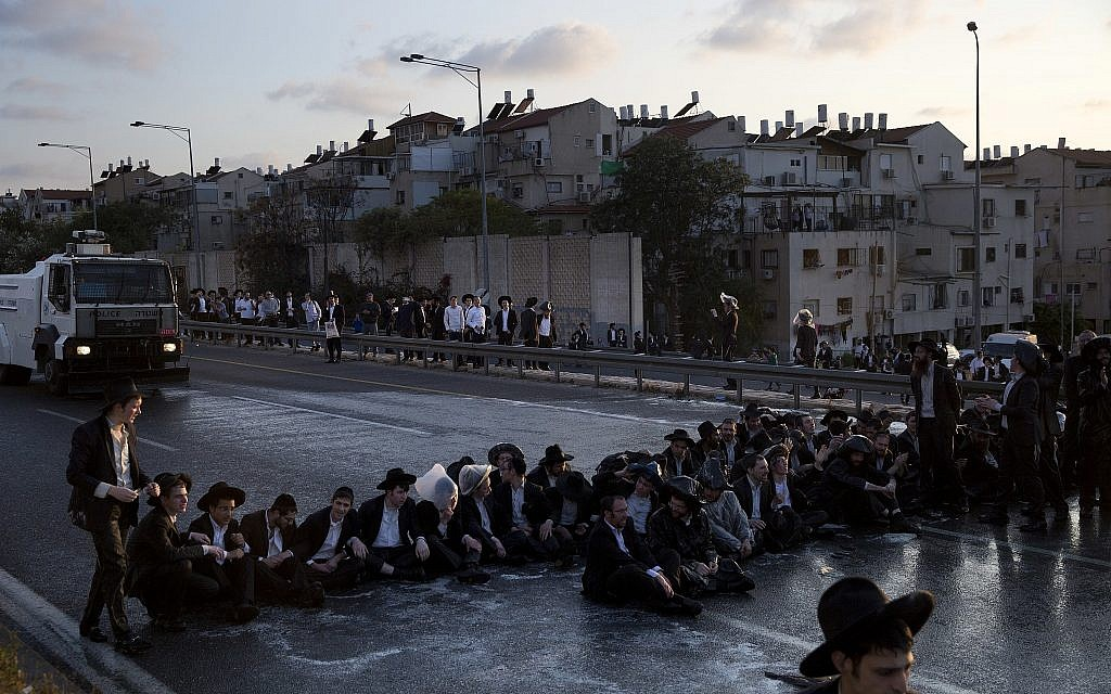 Ultra-Orthodox Jewish men block a highway during a protest against the detention of a member of their community who refused to serve in the military service, in Bnei Brak, Israel, March 12, 2018. (AP/Oded Balilty, File)