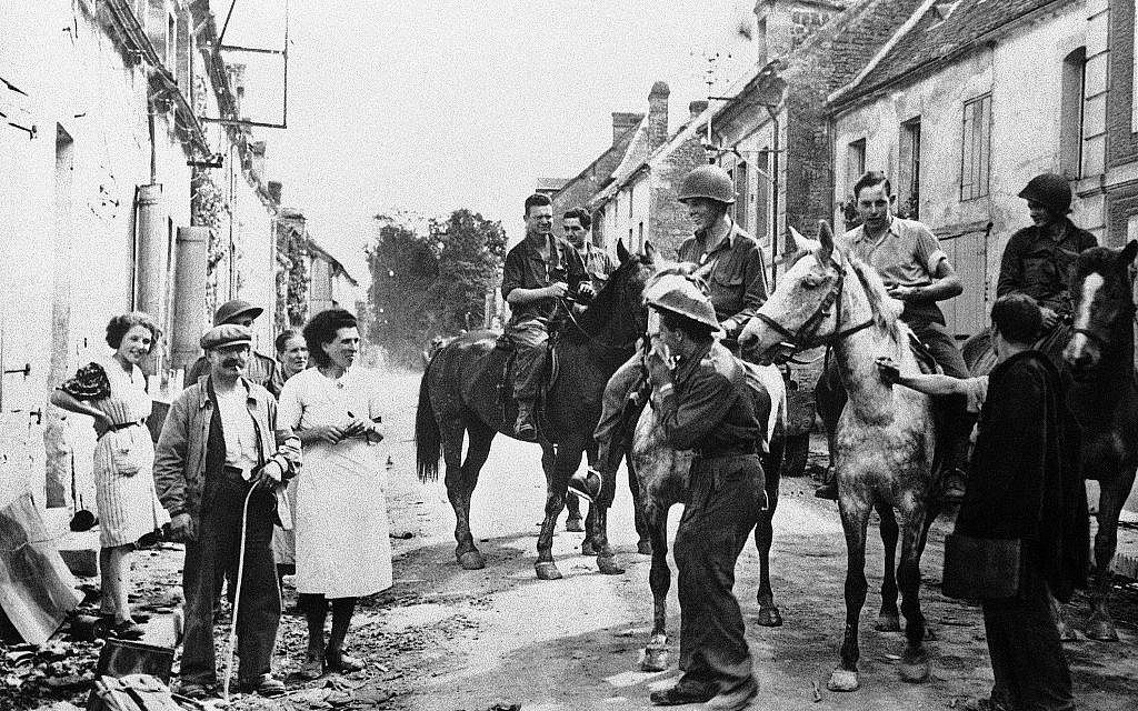 In this August 30, 1944 file photo, American soldiers riding horses captured from the retreating Germans are met by town residents as they enter the French town of Chambois, Normandy, France. D-Day marked only the beginning of the Allied struggle to wrest Europe from the Nazis. A commemoration Tuesday, June 4, 2019 served as a reminder of this, in the shadow of bigger D-Day 75th anniversary commemorations. (AP Photo, File)