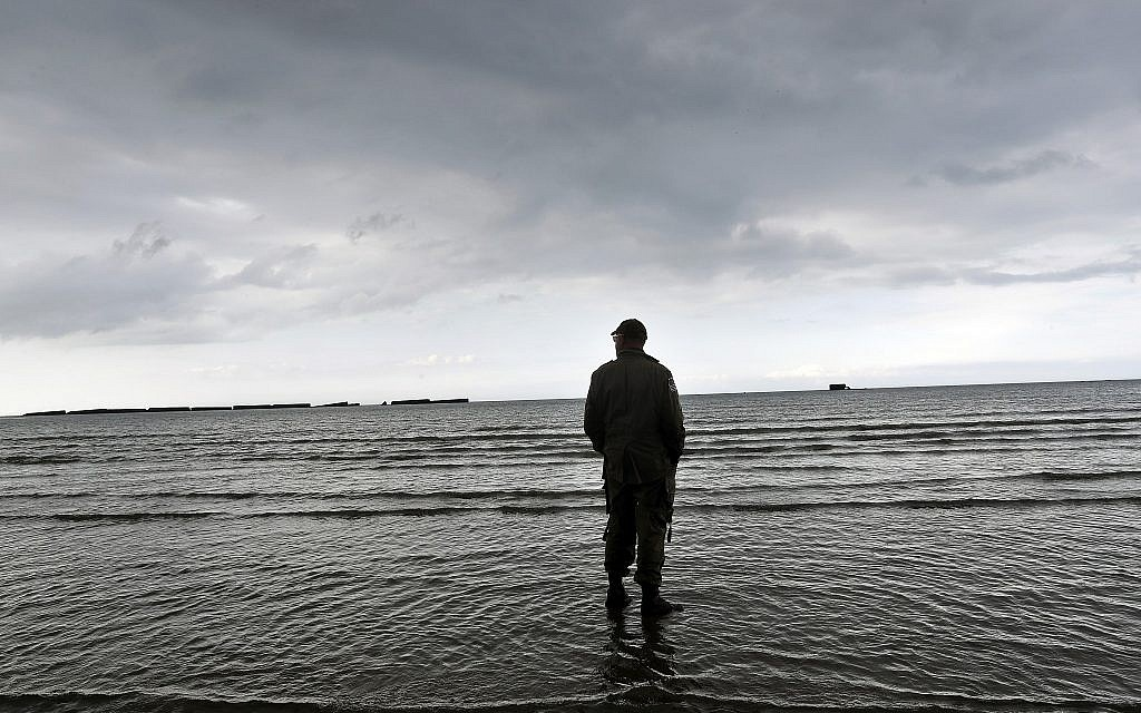 An enthusiast stands on the beach of Arromanches, June 4, 2019 in Normandy. Extensive commemorations are being held in the UK and France this week to honor the nearly 160,000 troops from Britain, the United States, Canada and other nations who landed in Normandy on June 6, 1944 in history's biggest amphibious invasion. (AP Photo/Thibault Camus)