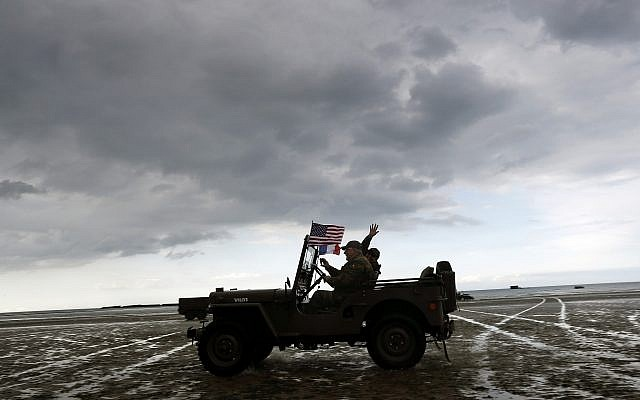 Enthusiasts ride a jeep on the beach of Arromanches, June 4, 2019 in Normandy. Extensive commemorations are being held in the UK and France this week to honor the nearly 160,000 troops from Britain, the United States, Canada and other nations who landed in Normandy on June 6, 1944 in history's biggest amphibious invasion. (AP Photo/Thibault Camus)