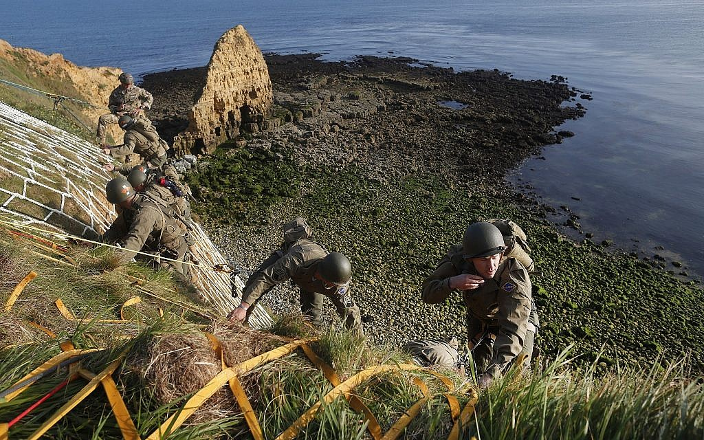 Soldiers from the US 75th Ranger Regiment, in period dress, climb the cliff of Pointe-du-Hoc in Cricqueville-en-Bessin, Normandy, France, June 5, 2019. During the American assault of Omaha and Utah beaches on June 6, 1944, US Army Rangers scaled the 100-foot cliffs to seize German artillery pieces that could have fired on the American landing troops. (AP Photo/Thibault Camus)
