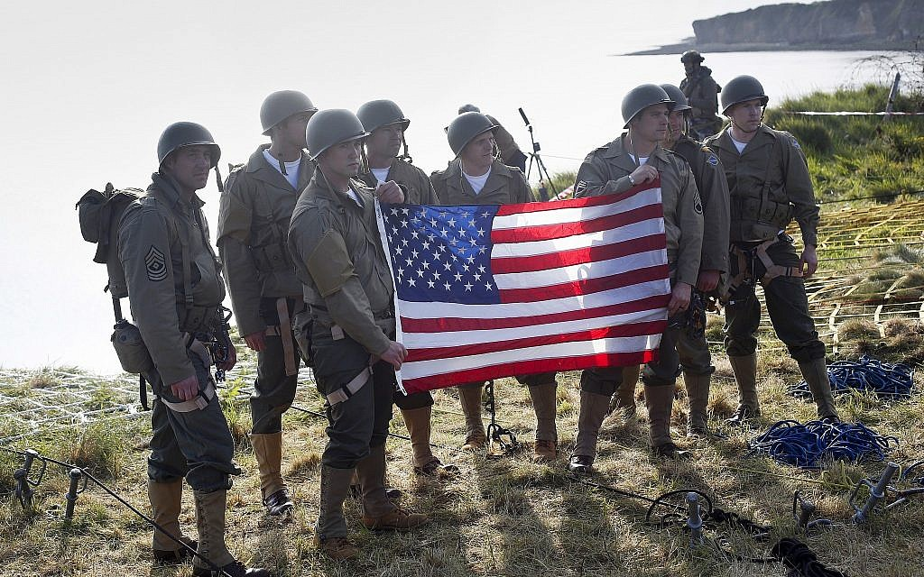 Rangers from the US 75th Ranger Regiment, in period dress, hold the American flag after scaling the cliffs of Pointe-du-Hoc in Cricqueville-en-Bessin, Normandy, France, on June 5, 2019. During the American assault of Omaha and Utah beaches on June 6, 1944, US Army Rangers scaled the 100-foot cliffs to seize German artillery pieces that could have fired on the American landing troops. (AP Photo/Thibault Camus)