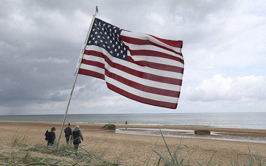 People walk on Omaha Beach, Normandy, where an American flag is planted, on June 5, 2019. Extensive commemorations are being held in the UK and France to honor the nearly 160,000 troops from Britain, the United States, Canada and other nations who landed in Normandy on June 6, 1944 in history's biggest amphibious invasion. (AP Photo/David Vincent)