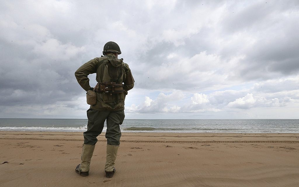 French enthusiast Julien watches the English Channel from Omaha Beach, Normandy, June 5, 2019, amid commemorations in the UK and France to honor the nearly 160,000 troops from Britain, the United States, Canada and other nations who landed in Normandy on June 6, 1944 in history's biggest amphibious invasion. (AP Photo/David Vincent)