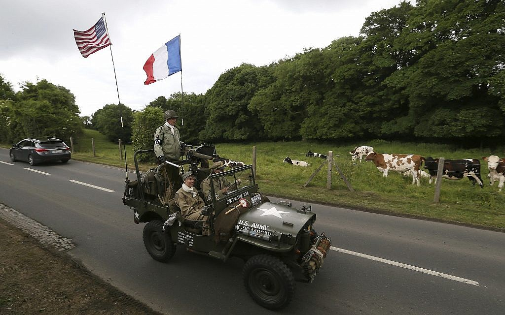 Cows watch WWII enthusiasts driving a jeep in Colleville-sur-Mer, Normandy, June 5, 2019. Extensive commemorations are being held in the UK and France to honor the nearly 160,000 troops from Britain, the United States, Canada and other nations who landed in Normandy on June 6, 1944 in history's biggest amphibious invasion. (AP Photo/David Vincent)
