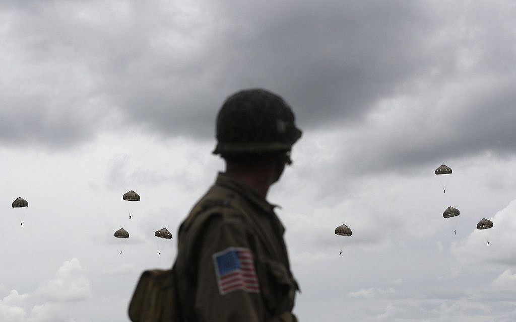 A WWII enthusiast watches French and British parachutists jumping during a commemorative parachute jump over Sannerville, Normandy, June 5, 2019. Extensive commemorations are being held in the UK and France to honor the nearly 160,000 troops from Britain, the United States, Canada and other nations who landed in Normandy on June 6, 1944 in history's biggest amphibious invasion. (AP Photo/Thibault Camus)