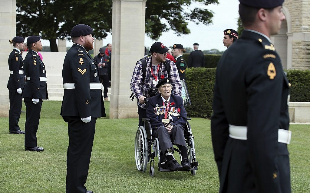 Canadian World War II veteran Jim Warford, center, arrives for a ceremony at the Beny-sur-Mer Canadian War Cemetery in Reviers, Normandy, France, June 5, 2019. The cemetery contains 2,049 headstones marking the dead of the 3rd Division and graves of 15 airmen who died on D-Day in World War II. (AP Photo/David Vincent)