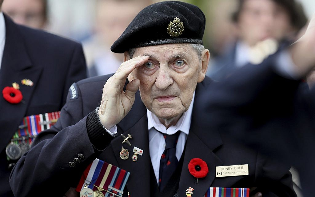 Canadian World War II veteran Sidney Cole salutes as he attends a ceremony at the Beny-sur-Mer Canadian War Cemetery in Reviers, Normandy, France, June 5, 2019. The ceremony was held for Canadians who fought and died on the beaches and in the bitter bridgehead battles of Normandy during World War II. (AP Photo/David Vincent)