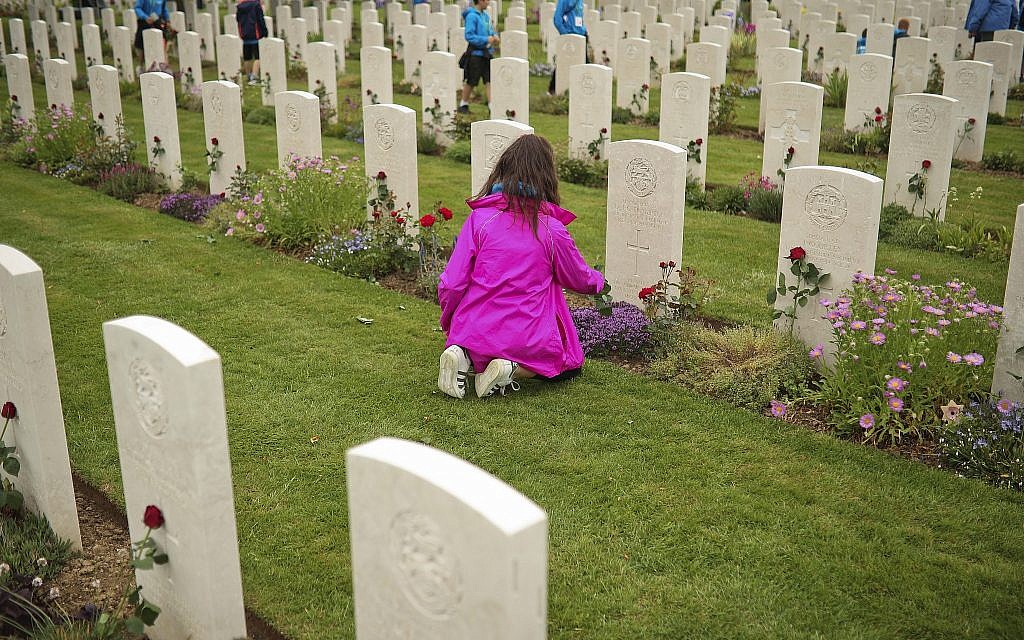 A young girl places a flower on the grave of a British soldier who fell in WWII, at the Bayeux War Cemetery in Bayeux, Normandy, France, June 5, 2019. Extensive commemorations are being held in the UK and France to honor the nearly 160,000 troops from Britain, the United States, Canada and other nations who landed in Normandy on June 6, 1944 in history's biggest amphibious invasion. (AP Photo/Francisco Seco)