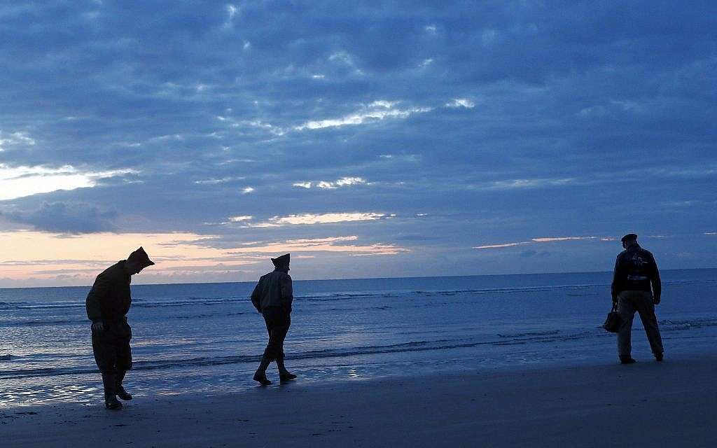 World War II reenactors walk along Omaha Beach, in Normandy, France, at dawn on June 6, 2019 during commemorations of the 75th anniversary of D-Day. (AP Photo/Thibault Camus)