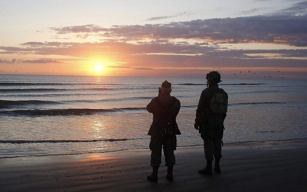 World War II reenactors stand looking out to sea on Omaha Beach, in Normandy, France, at dawn on June 6, 2019 during commemorations of the 75th anniversary of D-Day. (AP Photo/Thibault Camus)