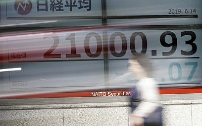 A woman walks past an electronic stock board showing Japan's Nikkei 225 index at a securities firm in Tokyo Friday, June 14, 2019. Asian shares were mixed Friday as investors weighed a variety of factors, including suspected attacks on two oil tankers in the strategic Strait of Hormuz and lingering worries about trade conflict between the US and China. (AP Photo/Eugene Hoshiko)