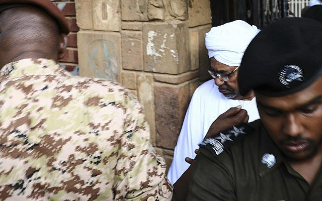 Sudan's ousted president Omar al-Bashir is escorted into a vehicle as he returns to prison following his appearance before prosecutors over charges of corruption and illegal possession of foreign currency, in Khartoum the capital of Sudan on Sunday June 16, 2019. (AP Photo/Mahmoud Hjaj)