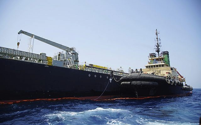 """The Panama-flagged, Japanese owned oil tanker Kokuka Courageous, that the U.S. Navy says was damaged by a limpet mine, is anchored off Fujairah, United Arab Emirates, during a trip organized by the Navy for journalists, Wednesday, June 19, 2019. The limpet mines used to attack the oil tanker near the Strait of Hormuz bore """"a striking resemblance"""" to similar mines displayed by Iran, a U.S. Navy explosives expert said Wednesday. Iran has denied being involved. (AP Photo/Fay Abuelgasim)"""