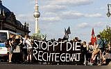 Picture taken June 18, 2019 shows people attending a protest ralley in Berlin, Germany, against far right violence. German police are investigating a series of threats sent to officials and institutions days after the arrest of a far-right extremist on suspicion of killing a pro-migrant politician. Slogan reads 'Stop Far Right Violence' (Christoph Soeder/dpa via AP)