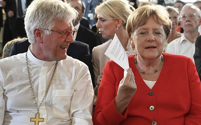 German Chancellor Angela Merkel fans herself as she sits next to Heinrich Bedford-Strohm, Council President of the Evangelical Church in Germany, during the annual reception of the Evangelical Church in Germany in Berlin on June 26, 2019. (Ralf Hirschberger/dpa via AP)