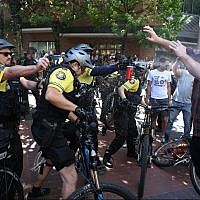 After a confrontation between authorities and protesters, police use pepper spray as multiple groups, including Rose City Antifa, the Proud Boys and others protest in downtown Portland, Ore., on Saturday, June 29, 2019. (Dave Killen/The Oregonian/AP)