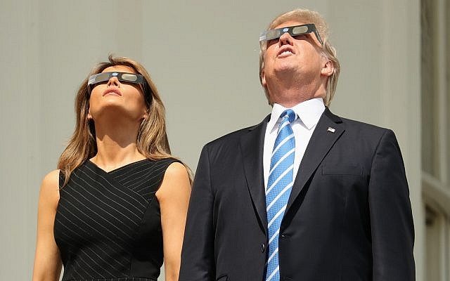 President Donald Trump, accompanied by first lady Melania Trump, holds up protective glasses as they arrive to view the solar eclipse, Monday, Aug. 21, 2017, at the White House in Washington. (AP Photo/Andrew Harnik)