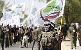 In this photo from July 1, 2016, members the Iran-backed Asaib Ahl al-Haq paramilitary group take part in a Quds Day march in Baghdad, Iraq. (AP Photo/Hadi Mizban, File)
