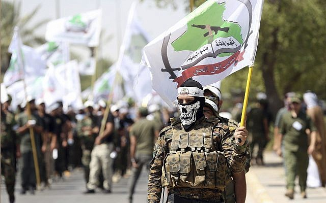 In this photo from July 1, 2016, members of the Iran-backed Asaib Ahl al-Haq paramilitary group take part in a Quds Day march in Baghdad, Iraq. (AP Photo/Hadi Mizban, File)