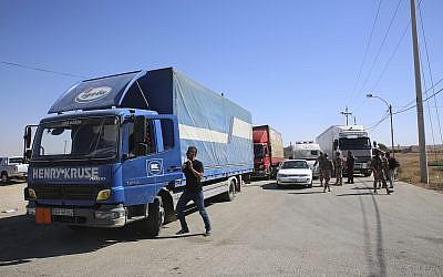 Trucks laden with aid for displaced Syrians wait to cross from Jordan to the Syrian side of the border, in Jabir As Sirhan, Jordan, July 1, 2018. (AP Photo/Omar Akour)