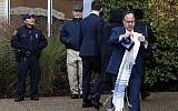 Illustrative: A worshiper walks past a Pittsburgh Police officer, and a private security guard outside the main entrance of the Beth Shalom synagogue after attending a Shabbat morning service on Nov. 3, 2018 in Pittsburgh. (AP Photo/Gene J. Puskar)
