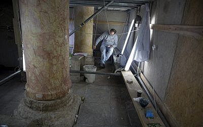 In this Thursday, Dec. 6, 2018 photo, a restoration expert works on a granite column inside the Church of the Nativity, built atop the site where Christians believe Jesus Christ was born, in the West Bank City of Bethlehem. (AP/Majdi Mohammed)