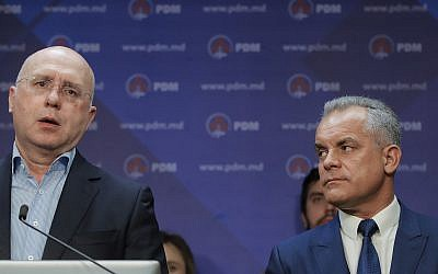 Vladimir Plahotniuc, the leader of the Democratic Party, right, watches Moldova's Prime Minister Pavel Filip speak during a press statement in Chisinau, Moldova, Sunday, Feb. 24, 2019.  (AP Photo/Vadim Ghirda)