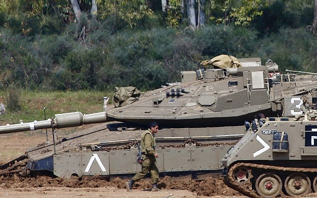 Israeli soldiers work next to their tanks near the Israel Gaza border, Israel, Tuesday, March 26, 2019.  (AP Photo/Ariel Schalit)