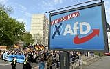 AfD supports walks along a party elections poster in Erfurt, Germany, Wednesday, May 1, 2019. The far-right Alternative for Germany launches its European parliament election campaign in the eastern city of Erfurt.(AP Photo/Jens Meyer)