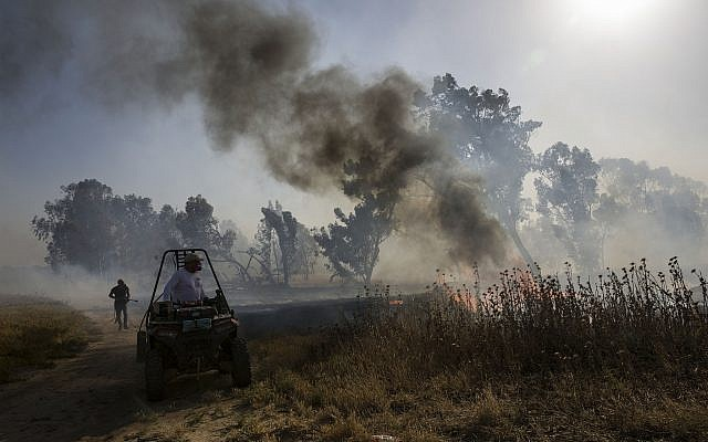 Illustrative: An Israeli firefighter battles a fire started by an incendiary device launched from the Gaza Strip, near the Gaza border fence, May 15, 2019. (AP/Tsafrir Abayov)