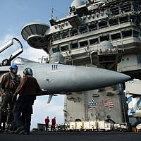 A pilot speaks to a crew member by an F/A-18 fighter jet on the deck of the USS Abraham Lincoln aircraft carrier in the Arabian Sea on June 3, 2019. (AP Photo/Jon Gambrell)