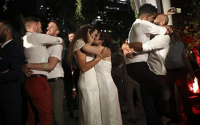 Gay couples take part in a mass same-sex wedding in Tel Aviv, Israel, Tuesday, June 4, 2019 (AP Photo/Oded Balilty)