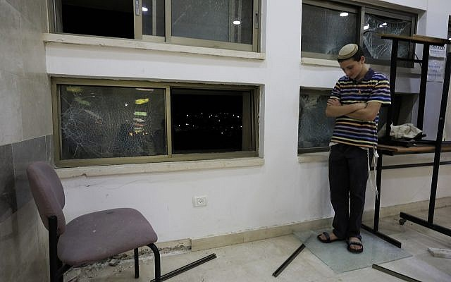 A student stands inside a Jewish religious school in Sderot, Israel, after it was hit by a rocket fired from the Gaza Strip, Thursday, June 13, 2019. (AP/Tsafrir Abayov)