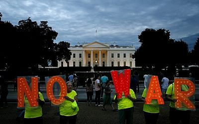 "Protesters hold signs spelling out, ""No War,"" outside the White House, Thursday June 20, 2019, in Washington, after President Donald Trump tweeted that ""Iran made a very big mistake"" by shooting down a U.S. surveillance drone over the Strait of Hormuz in Iran. (AP/Jacquelyn Martin)"