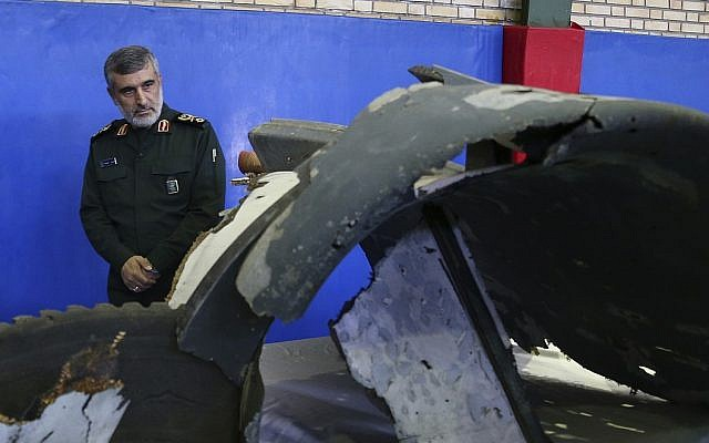 Head of the Revolutionary Guard's aerospace division Brig. Gen. Amir Ali Hajizadeh looks at debris from what the division describes as the US drone which was shot down on Thursday, in Tehran, Iran, Friday, June 21, 2019 (Meghdad Madadi/Tasnim News Agency/via AP)