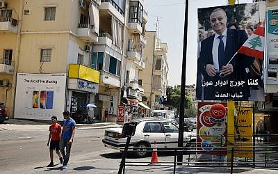 In this June 24, 2019 photo, a poster shows George Aoun, head of the municipality of the village of Hadat, with Arabic that reads 'We are all George Edward Aoun. Hadat youth,' in the Christian village of Hadat, where only Christians can rent or buy property, near Beirut, Lebanon (AP Photo/Bilal Hussein)